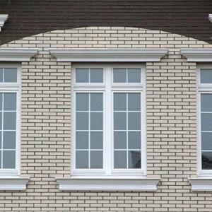 Обрамление оконных проемов на фасаде частного дома